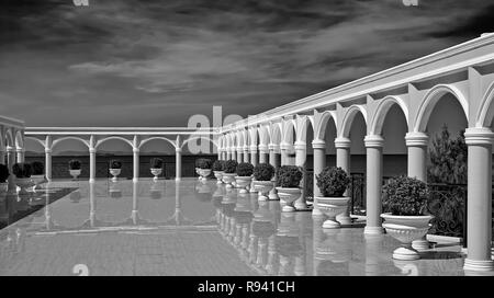Columns of an upper floor arched balcony area. Black and white photography - Stock Image