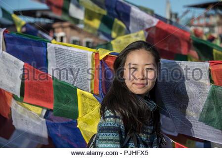 Nepal, Kathmandu, young Asian woman between the Tibetan prayer flags - Stock Image