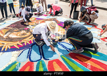 A member of Team Guatemala creates a floral carpet made from colored sawdust and decorated with flowers during the 8th Night Celebration marking the end of the Feast of St Michael in the central Mexican town of Uriangato, Guanajuato. Every year the town decorates 5km of road with religious icons in preparation for the statue of the patron saint to be paraded through the town. Uriangato became an international sensation after wowing Brussels with their floral carpet displayed at the Brussels Grand-Place during the Belgium Floral Carpet festival. - Stock Image