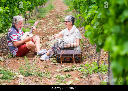 couple of alternative aged older traveler stay sitting down in a vineyard with the luggage and playing an ukulele acoustic guitar and reading a paper  - Stock Image