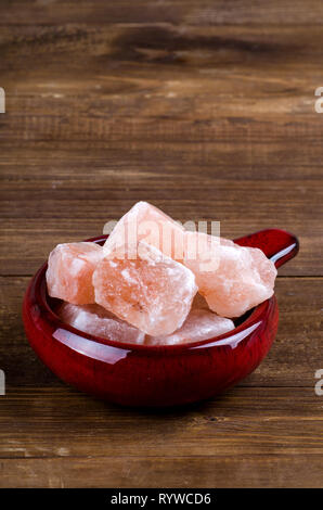 Himalayan pink rock salt on wooden background - Stock Image