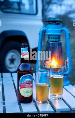 Tanzania, Serengeti. 'It's Kili time!' - Chilled Kilimanjaro beer and a parafin lantern. - Stock Image