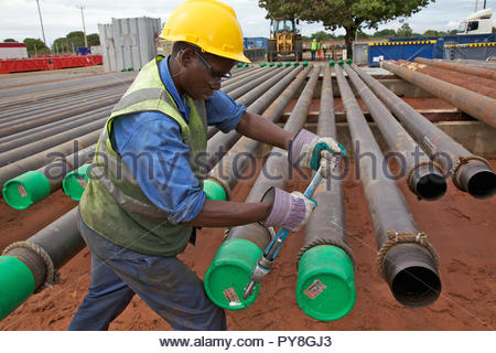 Man tightening lids of pipes - Stock Image