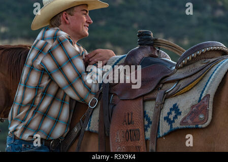 USA, California, Parkfield, V6 Ranch young smiling cowboy standing my his horse leaning on his saddle (MR) - Stock Image