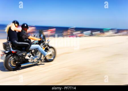 Motorcyclists ride on the beach sunbathing among people, Jurmala - Stock Image