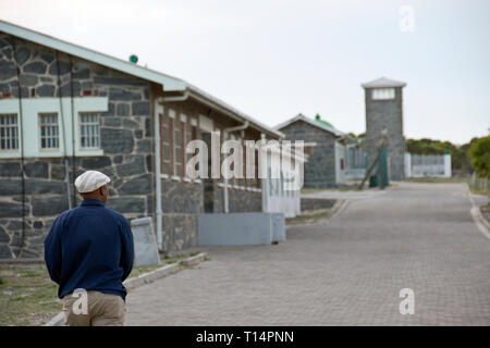 A tour guide strolls amongst the prison blocks at Robben Island, where Nelson Mandela was imprisoned during apartheid, Cape Town, South Africa. - Stock Image