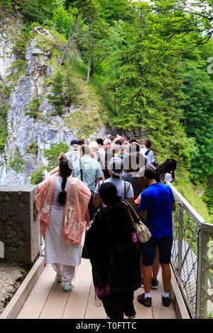 Tourists crowd onto the Marienbrucke bridge to get a view of Schloss Neuschwanstein, Munich, Bavaria, Germany - Stock Image