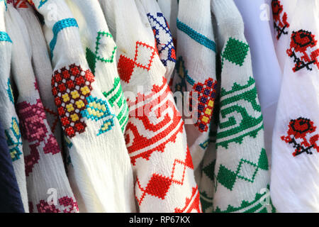 Colourful, tradtional clothes for sale on the market on Nicolae Balcescu Str, in Sibiu's old town, in Transylvania, Romania - Stock Image