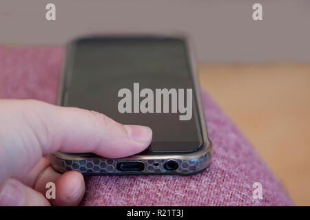 Thumb presses on a mobile phone to unlock the screen with a secure print - Stock Image