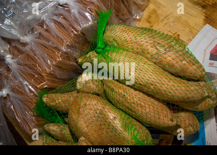 Sweet potatoes wrapped in green net bag vegetable produce market in San Antonio Texas Tx featuring local foods - Stock Image