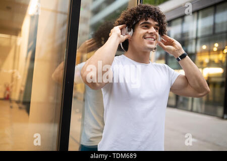 Happy sporty fit man running to stay healthy outdoor - Stock Image