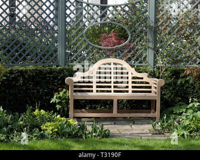 Ornate wooden bench in a garden - Stock Image