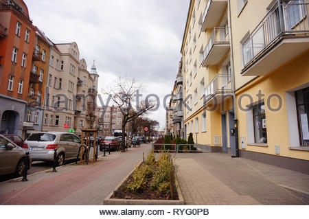 Poznan, Poland - March 8, 2019: Parked cars and apartment buildings on the Slowackiego street in the city center. - Stock Image