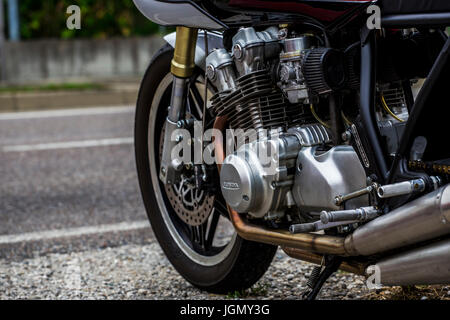 Engine and front wheel of a parked Honda motorcycle. - Stock Image