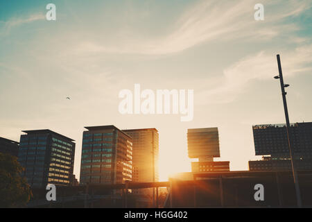 Sunset in Barcelona with many houses in distance, street lantern in front, evening teal sky with strong sun flare - Stock Image