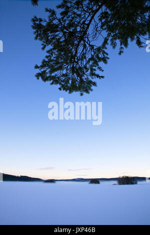Wide angle photograph of a frozen lake in winter at dusk. - Stock Image