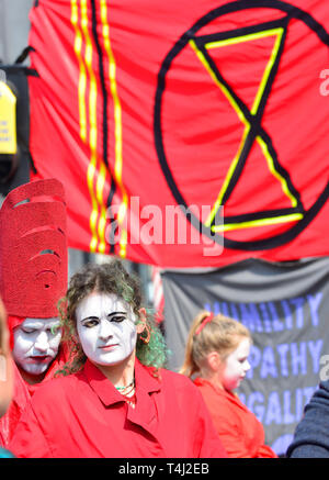 London, UK. 17th April, 2019. Environmental campaign group Extinction Rebellion bring traffic to a standstill in central London for the third day running, camping out in several locations around the city, to demand that the Government take emergency action on the climate and ecological crisis. Members of the 'Invisible Circus' prepare to perform in Oxford Circus. Credit: PjrFoto/Alamy Live News - Stock Image