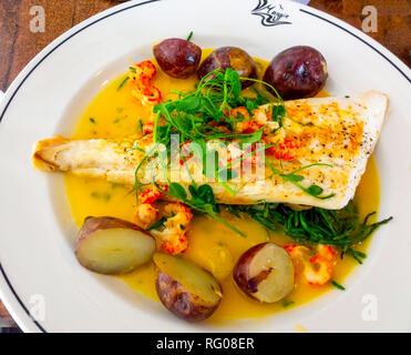 Lunch at then famous Magpie Café in Whitby  Halibut and Crayfish tails served with butter shallots and samphire with black potatoes - Stock Image