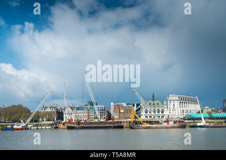 Cranes on barges on the River Thames working on the installation the new Super Sewer on the Albert  Embankment in London. - Stock Image
