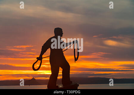 Newlyn, Cornwall, UK. 5th Apr, 2019. UK Weather. A cold but calm and colourful start to the morning at Newlyn looking out to Mounts Bay. Seen here Tom Leapers bronze memorial statue to Newlyn Fishermen silhoutted against the sunrise. Credit: Simon Maycock/Alamy Live News - Stock Image