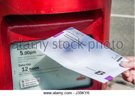 A woman posts her Postal vote before the last post on the eve of the inaugural Liverpool City Region Mayoral Election, - Stock Image