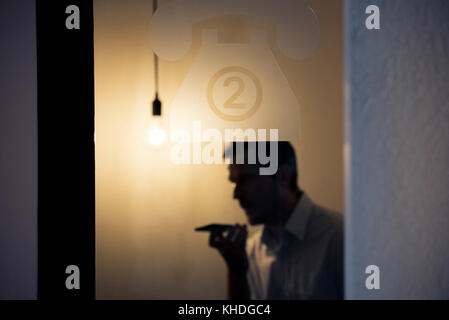 Man talking on mobile phone behind glass door - Stock Image