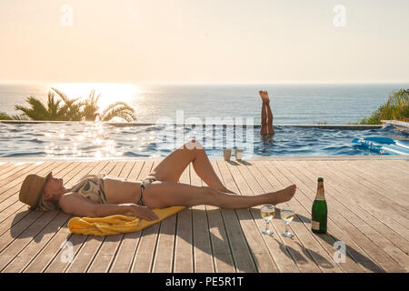 A woman wearing a bikini and a straw hat sunbathes on the decking by an infinity pool while someone does a handstand in the water behind her - Stock Image