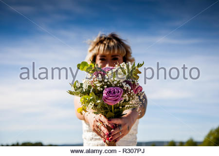 Bride poses with her bouquet under a blue sky - Stock Image