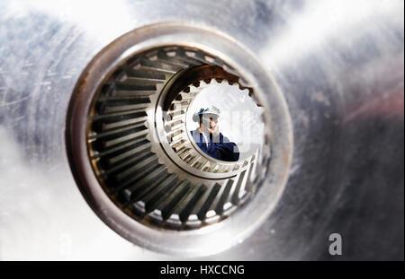 engineer, mechanic talking in phone, inside large gear axle - Stock Image