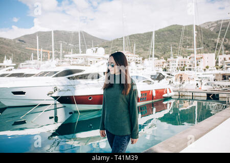 Young beautiful stylish girl walks along the promenade with yachts in Porto Montenegro in Tivat in Montenegro. - Stock Image