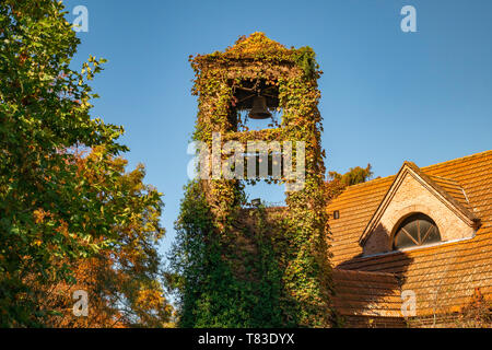 Yellows, reds and ochres in a bell tower in a sunny autumn park. The colors and luminosity of autumn take over this rural image in the suburbs. - Stock Image