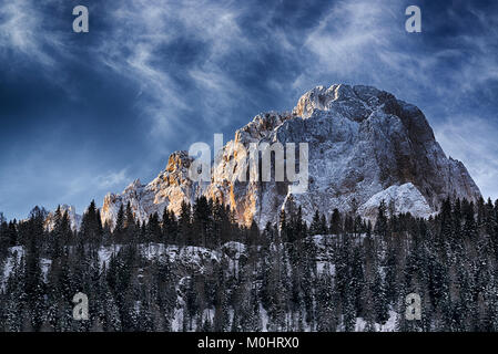 First ray of Sun on the top of mountain Sassolungo in winter morning - Stock Image