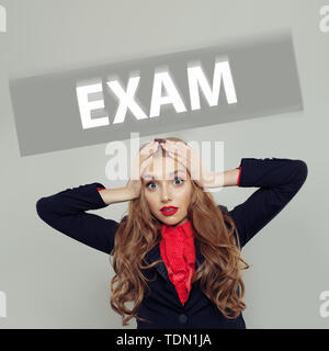 Scared student woman with exam inscription - Stock Image