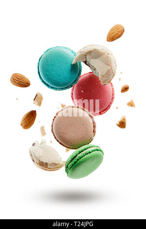 French macarons with almonds crushed into pieces. Colorful macaroons on white background. - Stock Image