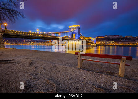 Budapest, Hungary - Bench at the beautiful Szechenyi Chain Bridge in unique blue colour with Buda Castle Royal Palace at background at dusk - Stock Image