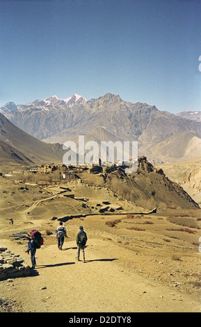 Trekkers descending from Muktinath to Jharkot with its old fort on Annapurna circuit Nepal Himalayas Kali Gandaki - Stock Image