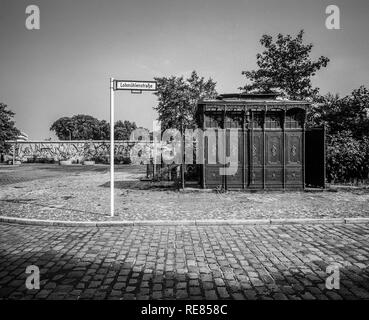 August 1986, ancient public toilet 1899, Berlin Wall graffitis, Lohmühlenstrasse street sign, Treptow, West Berlin side, Germany, Europe, - Stock Image