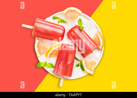 Red prange and grapefruit juice popsicles on pastel background. - Stock Image