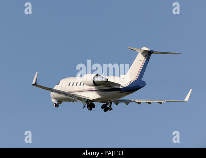 Boeing Company Bombardier Challenger 605 climbing out after take-off with undercarriage retracting - Stock Image