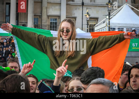 London, UK. 17th Mar, 2019.  A young woman wrapped in the Irish flag clearly enjoys her Paddy's Day. Following the spectacular St Patrick's Day Parade earlier, people celebrate and watch performances on Trafalgar Square in the heart of London. Credit: Imageplotter/Alamy Live News - Stock Image