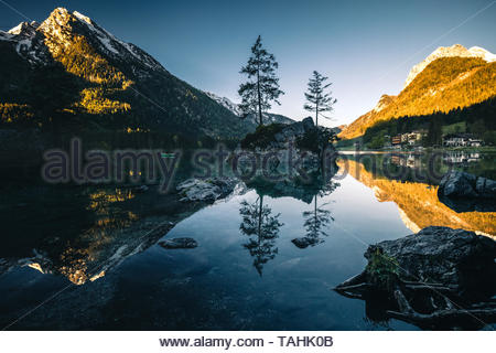 Fantastic sunrise at Hintersee lake. Beautiful scene of trees on a rock island during Spring in Berchtesgaden Germany - Stock Image