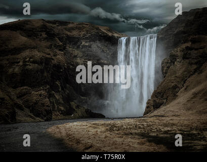 Majestic and dark Skogafoss waterfall in Iceland in a stormy day, moody atmosphere - Stock Image