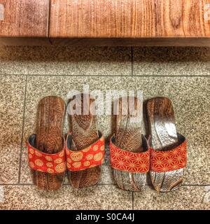 Two pairs of Japanese wooden sandals with orange geometric fabric pattern. - Stock Image