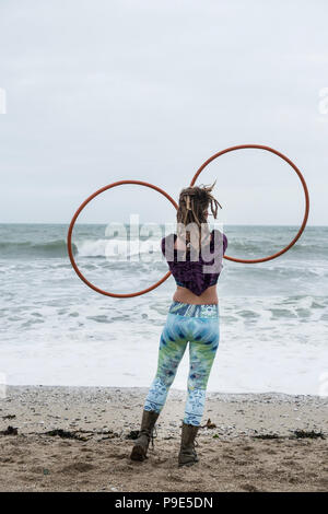 Young woman with brown hair and dreadlocks standing on a sandy beach by the ocean, balancing two hula hoops. - Stock Image