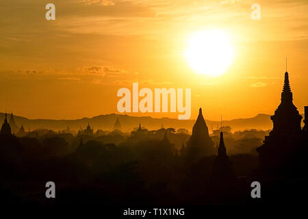 Early morning bright golden sun silhouettes ancient pagodas and temples of Bagan, Myanmar. - Stock Image