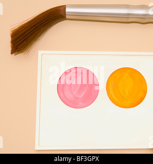 Palette of watercolor paints with a paintbrush mounted on a wall - Stock Image