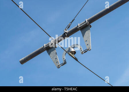 Electricity poles and lines at Seaton tramway, Devon, Uk, with a blue sky behind. - Stock Image