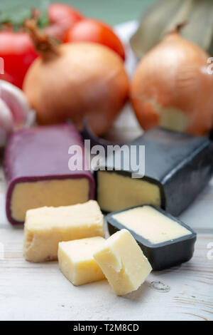 Mini black and dark red waxed cheddar cheeses with strong flavor made from West Country milk and and age-old methods with onion and garlic in England  - Stock Image