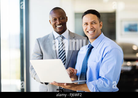 handsome workers standing inside car showroom - Stock Image