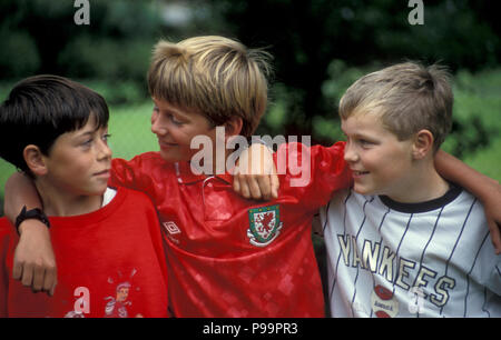 three young boys chatting on football field - Stock Image